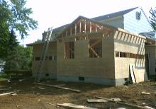 The roof is completely framed, and the sheething is going on. Nailing is important here.