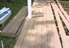 The composite decking boards get predrilled, and then screwed onto the joists.