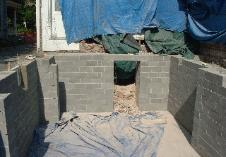 The block work is done. That doorway in the back is to the old stone foundation which we will have to break through.
